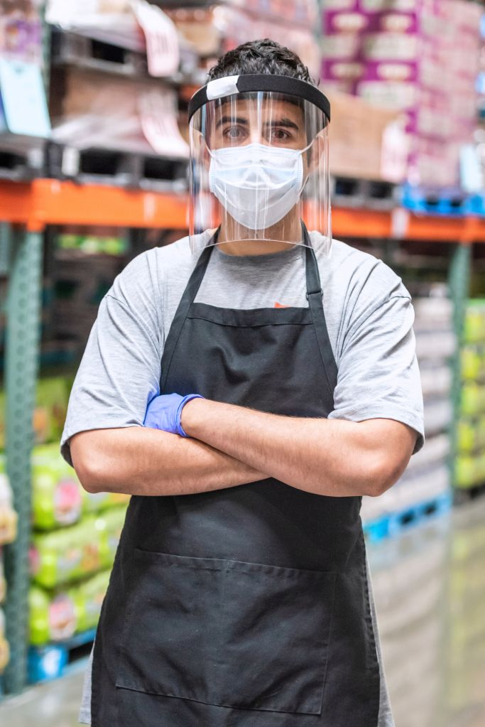 Megastore employee wearing a protective face mask and a face shield